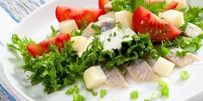 Селедочный салат с помидорами, картофелем и сметанным соусом