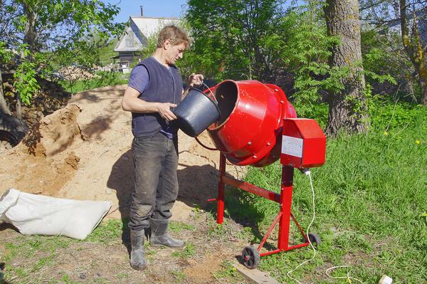 Мужчина готовит раствор в бетономешалке на дачном участке