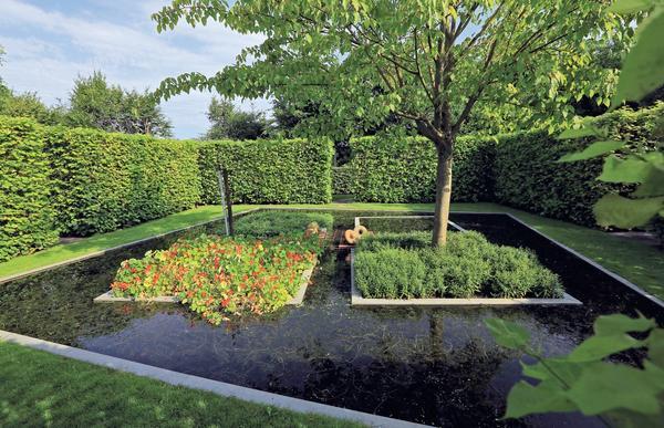 Геометрию зеленых экранов-стен органично повторяют очертания садового пруда