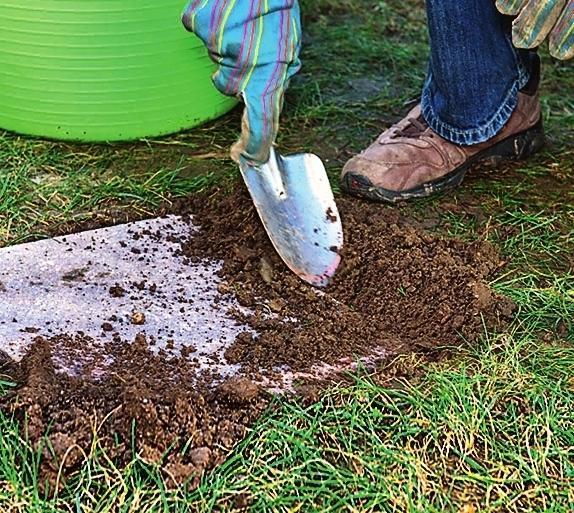 Заполните землей щели между плитами и газоном, хорошенько ее вдавите.