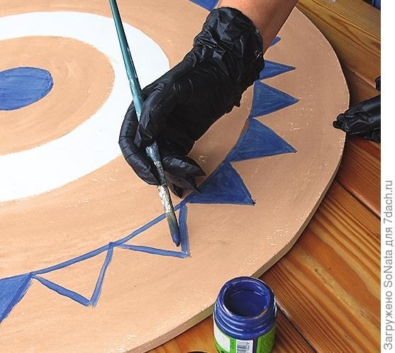 Закрасьте кружок в середине столешницы синей краской. По краю столешницы нарисуйте узор из синих зубцов, а затем - белую зигзагообразную линию. Когда столешница высохнет, покройте ее матовым лаком для дерева.