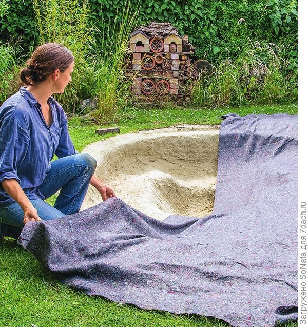 Для того чтобы защитить пленку, наполните котлован песком слоем около 10 см. Сверху положите мягкий геотекстиль.