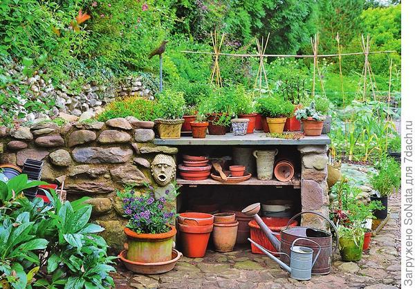 Садовый стеллаж можно встроить в подпорную стенку, сложенную из булыжников-окатышей среднего размера.