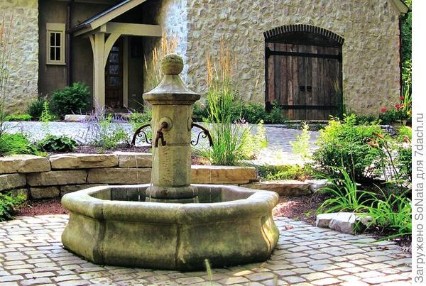 Средиземноморский стиль в саду создает восьмиугольный фонтан с колонной.