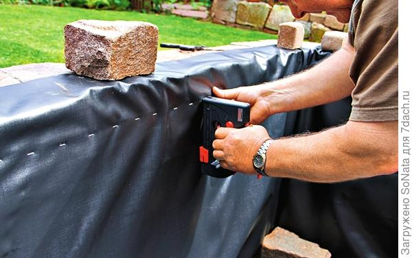 К внутренней стенке водоема с помощью раствора прикрепили деревянную рейку, а к ней - пленку для пруда.