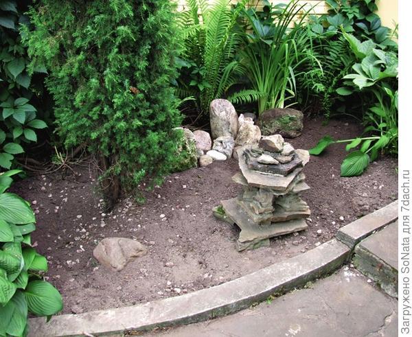 Очистите выбранное место от сорняков. Положите несколько крупных красивых камней.