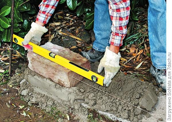 Установите на фундамент камень из песчаника, проверив прямолинейность с помощью уровня.
