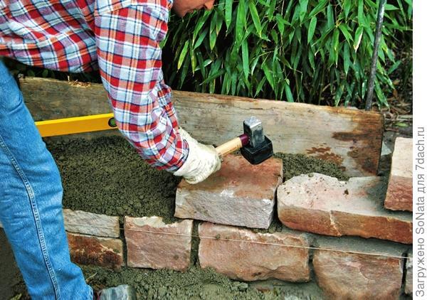 Используя резиновый молоток, вбивайте камни в раствор.