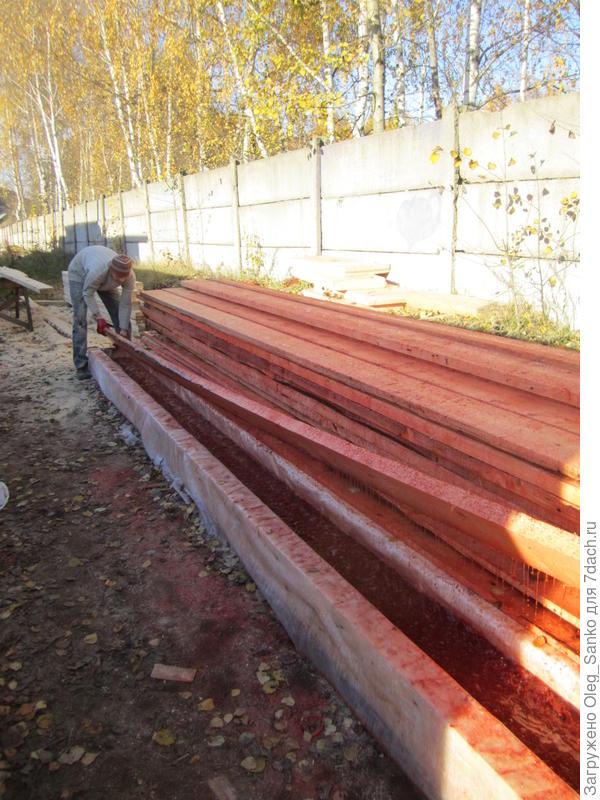 Погружение деревянного строительного элемента в лоток с защитным раствором.