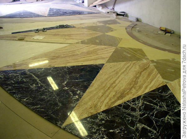 Процесс работы по укладке розетки из мрамора.