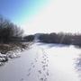 Лучи солнца скользят по припорошенной снегом поверхности реки.
