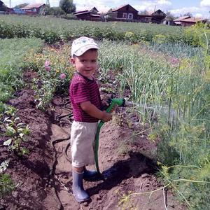 Юный агроном поливает огород