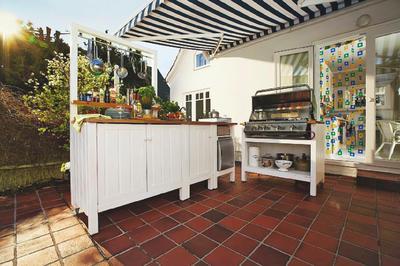 Самое практичное решение - расположить летнюю кухню рядом с домом