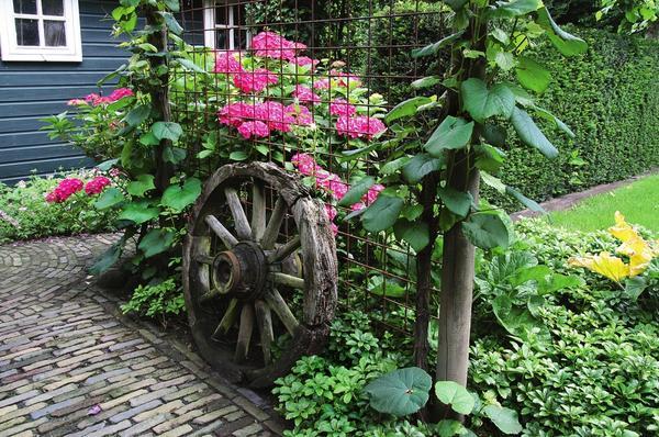 Колесо от старой телеги станет стильным акцентом в оформлении придомовой территории.