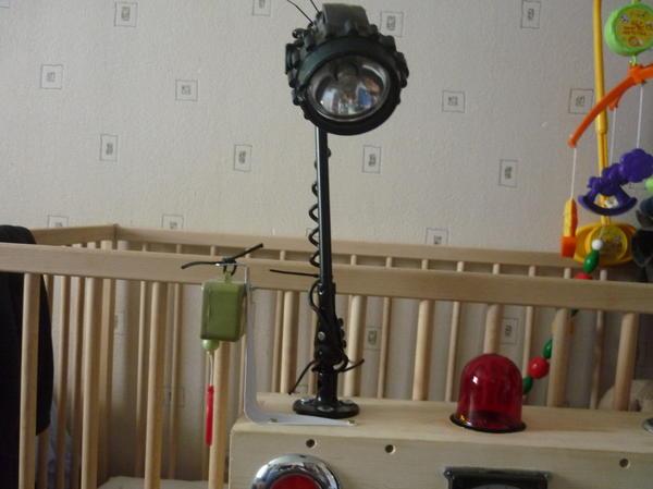 Два светильника, один от шахтерского фонаря, крепится на штанге с самолета, можно изменять направление освещения. Сбоку прикреплена коробочка с музыкальной игрушки.