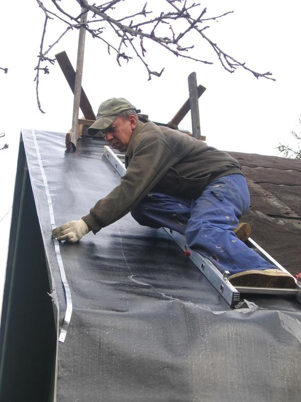 Монтажник фиксирует полотно рубероида стальной шиной