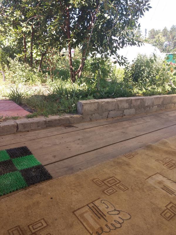 Веранда стоит на фундаменте, с трёх сторон выложен ряд кирпича и к на участке перепад высот.