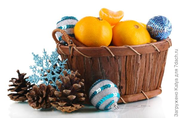 корзина с новогодними украшениями и мандаринами