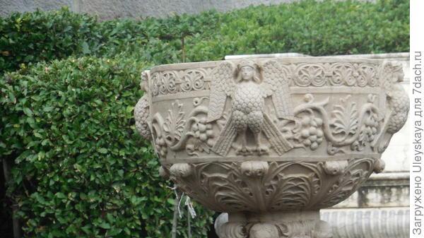 По центру интересная каменная ваза на высокой ножке