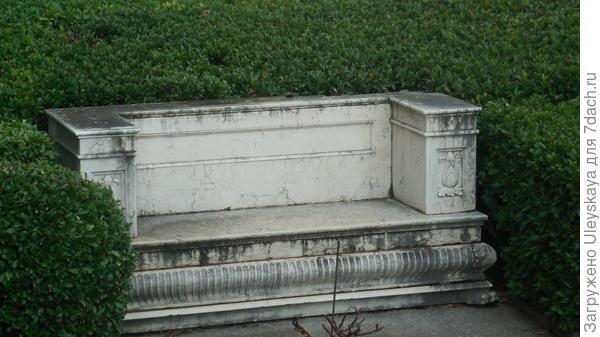 Каменный диван гармонично вписан в живую изгородь