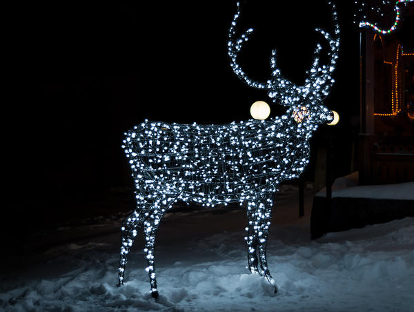 Фигура оленя из проволоки, украшенная светящейся гирляндой, привлекает внимание