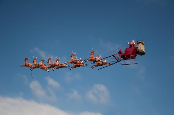 Олени запряжены в повозку Санта-Клауса, развозящего новогодние подарки