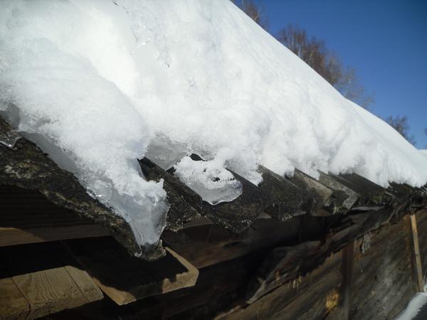 Снег на крышах быстро тает под солнечными лучами