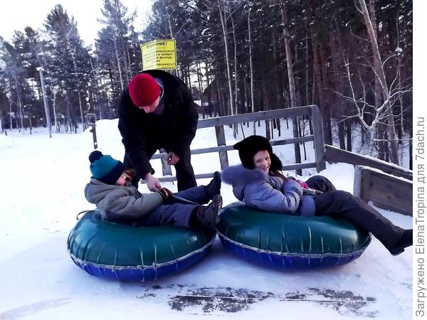 Лола и Дима готовятся съехать с горы на тюбах .
