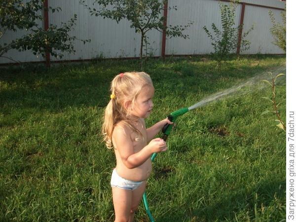 дочка поливает сад