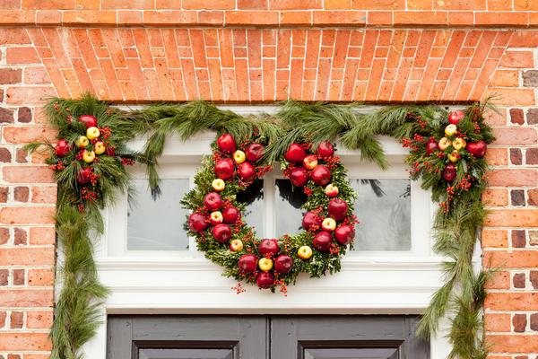 Традиционный вариант - повесить рождественский венок на входную дверь или над нею