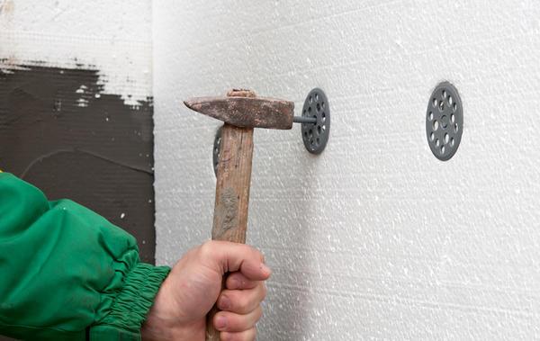 С помощью перфоратора и молотка закрепляем по пять дюбелей на каждый лист утеплителя