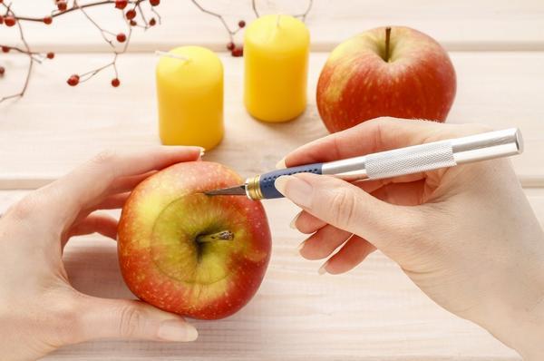 Берем яблоко и острым ножом делаем сверху надрез по диаметру свечи