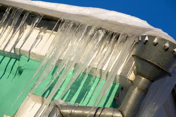 Тающий снег на скатах постепенно сползает, а талая вода замерзает на обдуваемых ветерком свесах крыши, образуя наледи и сосульки и закупоривая водосток