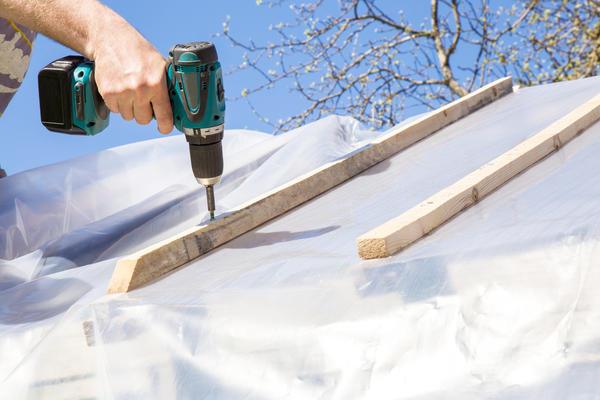Пленка прижимается к каркасу деревянными рейками и прикручивается саморезами
