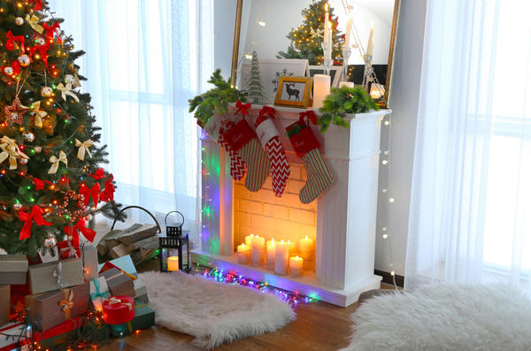 Если в гостиной у вас есть большое зеркало, поставьте новогоднюю ёлку так, чтобы она отражалась в нём