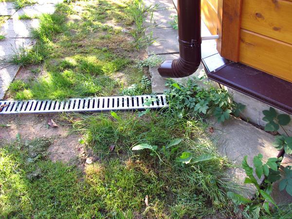 Водосточная труба, направленная в отверстие ливневой канализации