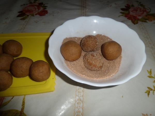От общей массы теста отщипываем небольшие кусочки и придаем форму колобков. Обваливаем их в смеси сахара и корицы.