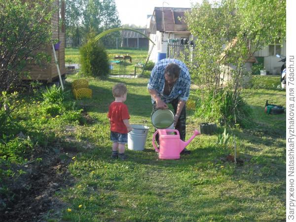 Ярослав набирает воду с дедушкой
