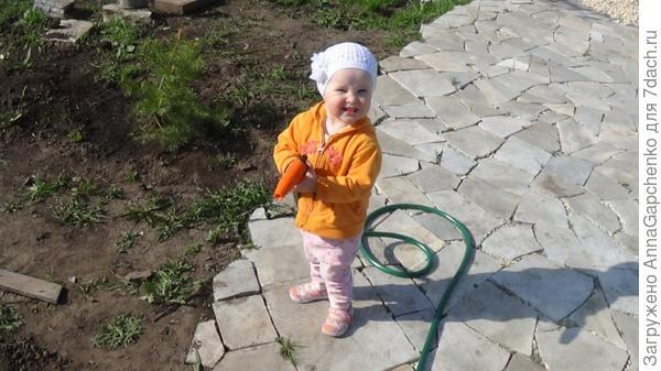 Ребенок поливает из шланга