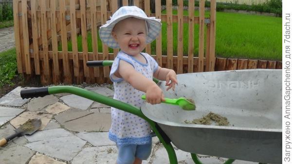 Ребенок загружает песок в тележку