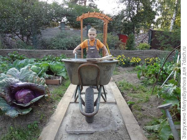 Костя помогает делать дорожки в огороде