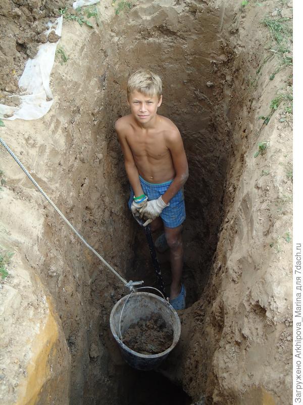 Сынок Роман Выкапывает яму под дренажный колодец.