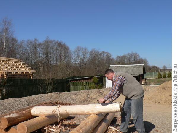 Муж ошкуривает подпорные столбы для подвала