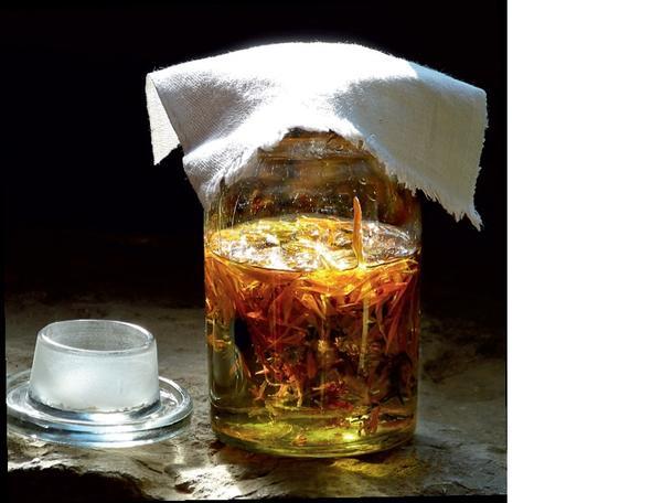 Цветки календулы и масло поместите в стеклянную банку