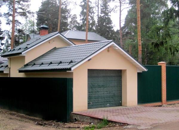 Облик гаража гармонично сочетается с солидной оградой земельного участка