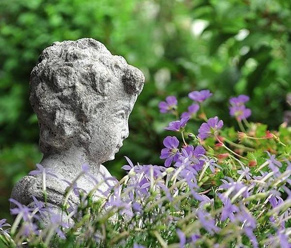 Мраморная фигурка в окружении нежно-голубых цветов