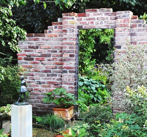 Большое зеркало на кирпичной стене словно открывает дверь в параллельную садовую реальность.