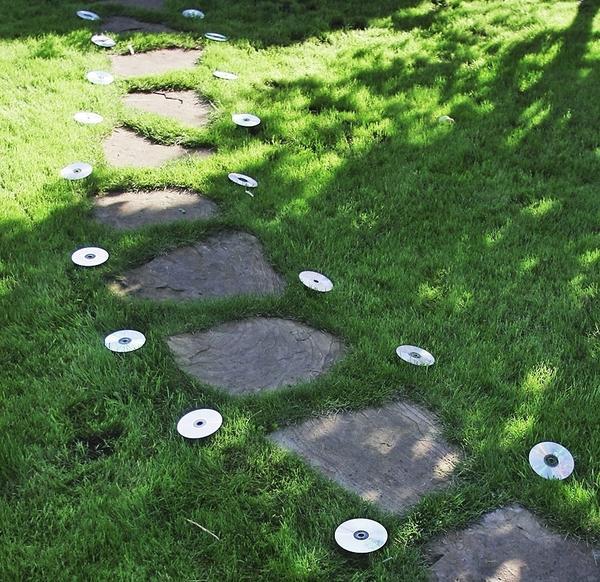 CD-диски способны превратиться в маленькие отражатели, если разложить их вдоль садовой тропинки и по центру закрепить колышками.