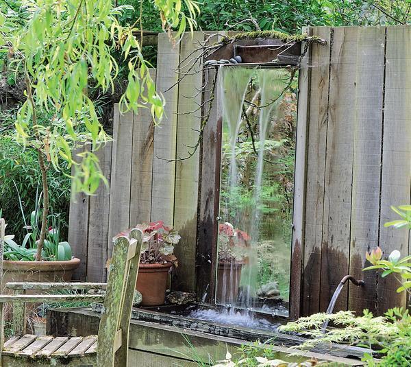Зеркальный фрагмент забора выглядит оригинально и позволяет любоваться садом с неожиданного ракурса. Фото: MoySad.