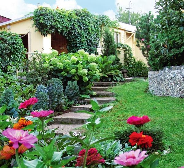 Удобные ступени садовой лестницы проложены прямо до крыльца небольшого, но очень уютного гостевого домика.
